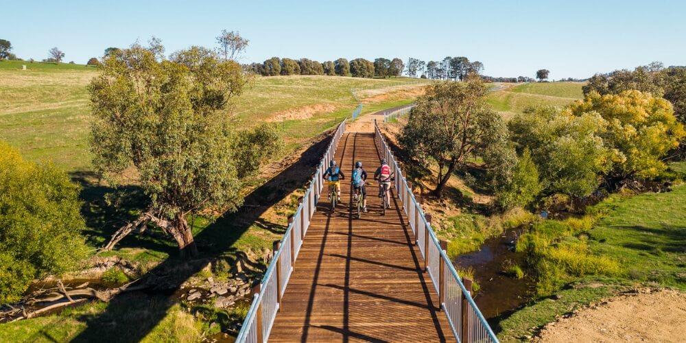 Cyclist riding across Tumbarumba to Rosewood Rail Trail Bridge Snowy Valleys
